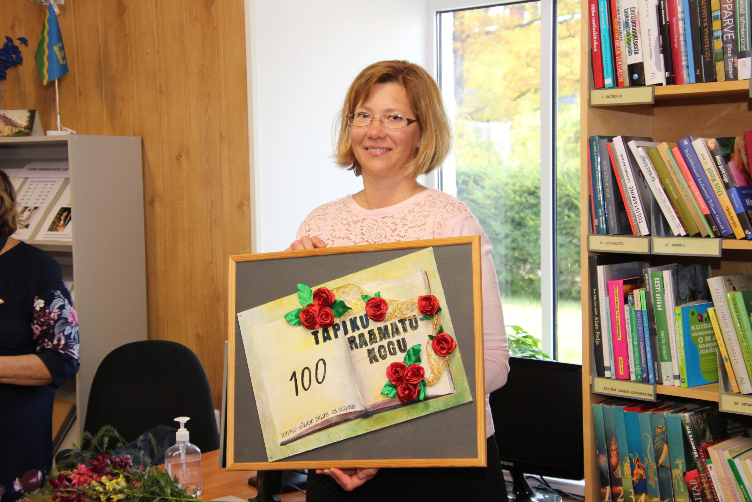 Tapiku raamatukoguhoidja Hiie Nugis koos kingituseks saadud ilusa kunstiteosega. Foto Raimo Metsamärt.